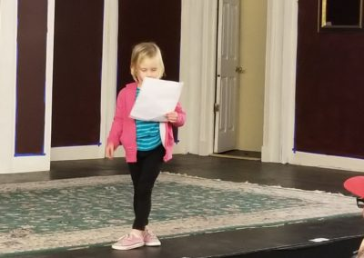 Kayla, age 5, reads her original poem about dogs and cats.